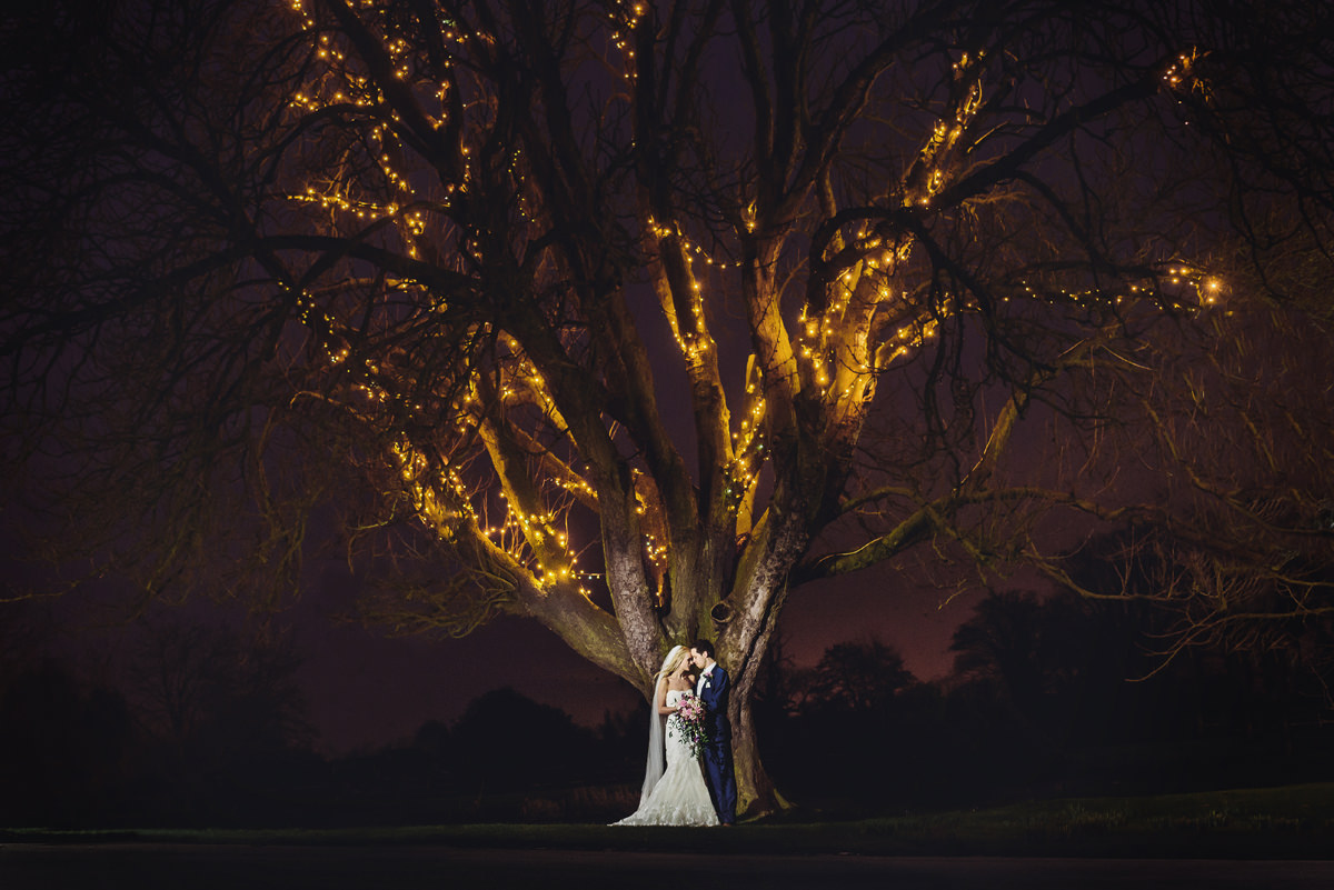 flash shot of couple under tree with fairy lights