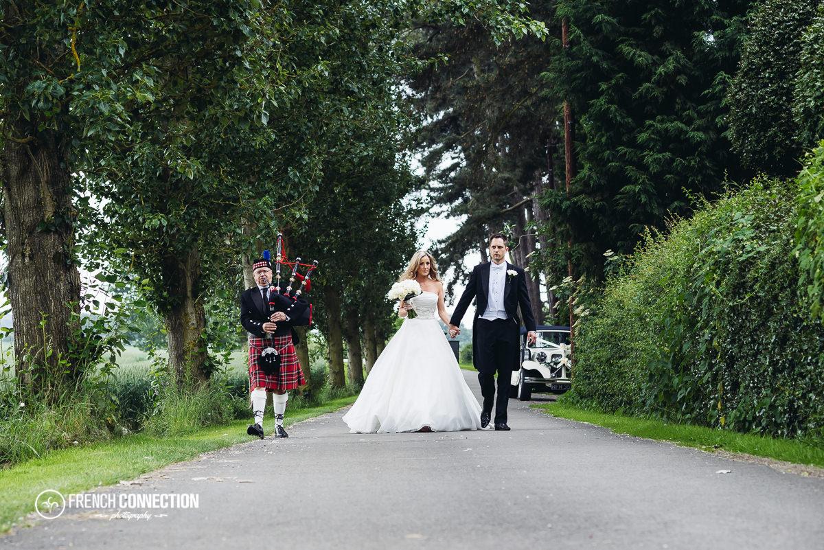 bride and groom walking along packington driveway
