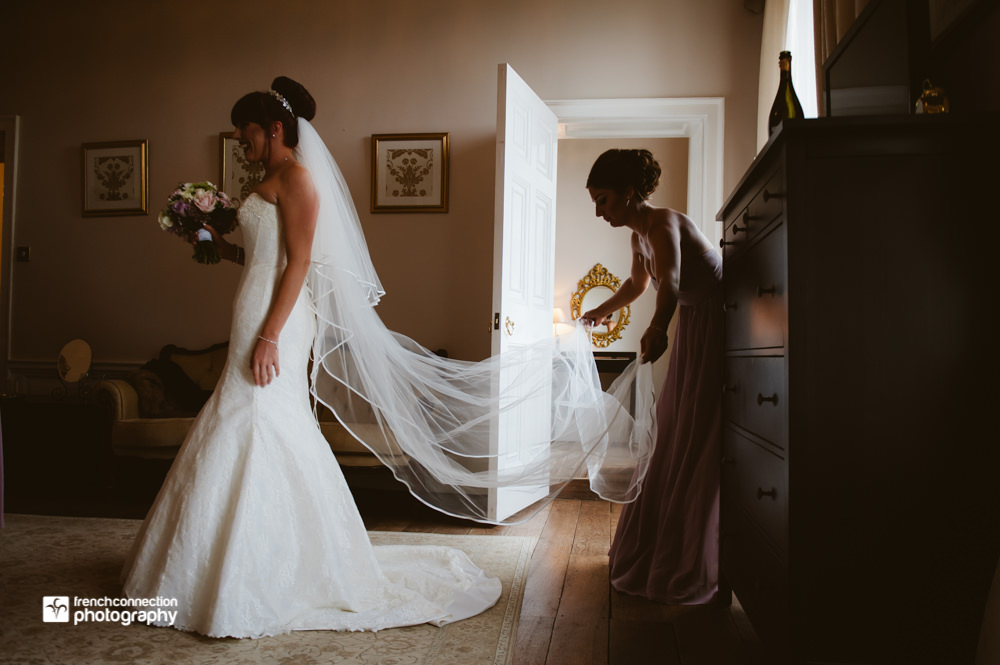 bridesmaid adjusting brides veil